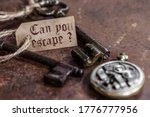 Small photo of two old keys on a rusty metal table with labels : can you escape ?