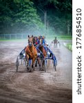 """Small photo of GRONINGEN NETHERLANDS - JULY 12, 2020: Riders compete during their harness racing or horse sulky race at the """"Royal Drafbaan Groningen"""""""