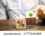 Small photo of Businessman holds wooden blocks with percent and up or down arrow. Mortgage and loan rates. Interest rate, stocks, ranking. Business and finance concept.