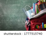 Small photo of Backpack full of school supplies with mask and gel protection for covid-19 with green blackboard with blank space for writing front view