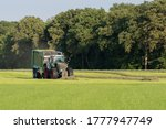 Green Tractor Picking Up Cut...