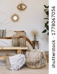 Small photo of Still life concept. Vertical photo of cozy apartment in boho chic style interior with comfort bedroom, fabric sheet plaid on bed, wooden bench seat, dry plants in vase, home decor in wicker basket