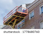 Worker Repairs The Facade Of A...