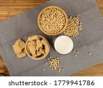 Soy foods collection with dry soy meat, soybeans, soy milk and tofu on rustic background top view. Soy products mix with curd, protein or TSP