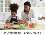 Small photo of Smiling young african American mother and small daughter chop vegetables prepare healthy vegetarian salad in kitchen, happy biracial mom teach little girl child cooking food at home, dieting concept