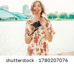 Portrait of young beautiful smiling hipster girl in trendy summer sundress.Sexy carefree woman posing on the sea background at sunset. Positive model holding retro camera