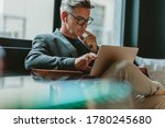 Small photo of Businessman looking at laptop and thinking. Businessman reading emails on laptop in office lobby.
