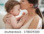 Young Mother Kissing Her...