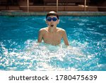 A little boy actively swims in the pool in the open air. The concept of sport and healthy lifestyle. Blured image, No focus, selective focus. - stock photo