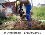 A Worker Is Drilling Soil For A ...