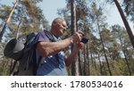 Low angle view of senior man on hiking trip taking photos in forest with digital camera. Retired male backpacker photographing nature during trekking trip. Active retirement, tourism and hobby concept - stock photo