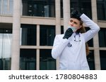 Small photo of Tired young girl doctor takes off medical mask. The concept of a doctor after a major operation