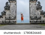 Bali, Indonesia. Traveler man jumping with energy and happiness in the gate of heaven. Lempuyang temple