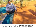 Small photo of Kings Creek Station, Northern Territory, Australia - Aug 21, 2019: aboriginal guide man creating shapes with red sand on the ground in aboriginal art style. Karrke Aboriginal Cultural Experience tour.