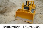 A Toy Yellow Bulldozer Digs Th...