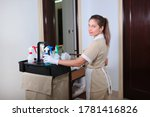 Maid with a trolley for room service. Concept of hotel business and cleaning. Cleaning products in the cart. Photo of the interior of the hotel. Copy space.
