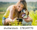 Stock photo teen girl taking photo of herself and her dog with mobile phone camera 178149770