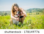 Stock photo young smiling woman showing something to her dog on smart phone outdoor in nature 178149776