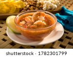 Small photo of Ecuadorian shrimp ceviche is a very popular dish in Ecuador. It's a cold soup with shrimp, with fresh tomato, lime and a bit of orange juice. Served with fried plantains, popcorn and toasted corn.