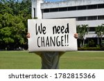 Small photo of Protester holds paper which has texts 'We need change!!', consept for protesting and voting someone else who can do something better at the moment and can change worse things to be the best things.