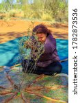 Small photo of Kings Creek Station, Northern Territory, Australia - Aug 21, 2019: Australian Aboriginal woman making a ritual on a bush painting. Karrke Aboriginal Cultural Experience tour in Australian outback.