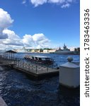 Small photo of A pier, to which a pleasure boat approaches, followed by warships in the water area of the Neva, arrived to participate in a naval parade in St. Petersburg.