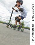 Small photo of A cute little boy rides a scooter in a skatepark. A young novice athlete spends free time in extreme sports. Motion photo, interchangeable motion blur.