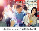 Small photo of Tipsy man trying to seduce young female colleague on office party at nightclub