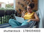 Young Woman Working On Balcony. ...