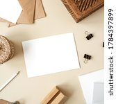 Small photo of Blank paper sheet on beige table. Artist home office desk workspace with wooden casket, pencil, envelopes and stationery. Wedding invitation card. Flat lay, top view mockup with empty copy space
