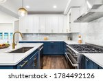 Small photo of CHICAGO, IL, USA - JUNE 7, 2020: A luxurious white and blue kitchen with gold hardware, Bosch and Samsung stainless steel appliances, and white marbled granite counter tops.