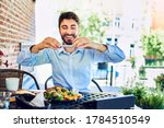Portrait of happy young man taking picture of breakfast in cafe outdoors - stock photo
