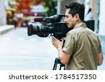Young cameraman using a...