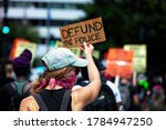 "Small photo of Washington, DC, USA - July 25, 2020: A protester carries a sign that says ""Defund the Police,"" during the March Against Trump's Police State, sponsored by the Party for Socialism and Liberation"
