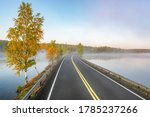 Small photo of Finnish landscape with narrow car road through the lake. Foggy early morning in autumn in Finland