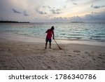 Small photo of Bodufolhudhoo / Maldives - August 17, 2019: Maldivian worker passing rake through beach sand at sunset