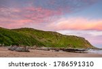 A pastel sunset over the Rosetta Bluff from the beach at Petrel Cove located on the Fleurieu Peninsula Victor Harbor South Australia on July 28 2020