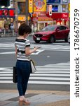 Small photo of TOKYO, Ueno Station Japan - July 29, 2020: woman is using smartphone while standing at a crosswalk. Inattentive female focused on the phone