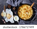 Oven baked cauliflower cheese - vegetable side dish, served on a black baking dish on wooden background with ingredients: garlic, nutmeg, peppercorns, milk, parmesan cheese, flat lay, close-up