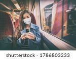 Small photo of Face mask concept. Woman wearing mandatory mask inside public spaces for transport such as train station and bus. Asian woman passenger using mobile phone with face covering on commute.