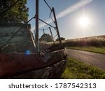 Abandoned boat wreck next to a path with backlight of the summer sun and a corn field and green grass - stock photo