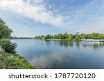 Small photo of Maas river with a boat anchored on its bank with a vehicular bridge in the background, abundant green vegetation on a sunny summer day with a blue sky and white clouds in South Limburg, Netherlands