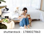 Small photo of Young Asian woman relaxing, holding and giving a treat to Shiba dog, White Shiba puppy and Maltese dog, smile happy against bed in bedroom. Pet therapy at home. Relationship of pet and owner concept.