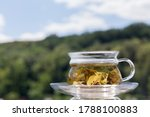 Cup of green tea in a blurred background. The background was a forest and sky with cloouds. Close-up.