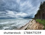 Small photo of Baltic sea coast (sand dunes) and pine forest under dramatic clouds after thunderstorm. Latvia. Epic seascape. Cyclone, gale, storm, rough weather, meteorology, climate change, natural phenomenon