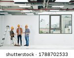 Young construction engineers in hard hats and plains shirts discussing news and gossips during short break at work - stock photo