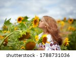 A beautiful girl in an embroidered shirt with fluttering hair sniffs a sunflower flower. Ukraine