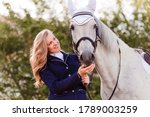 Small photo of Teenage girl smacks horse in snout against natural background