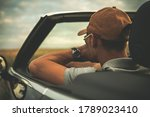 Caucasian Pensive Men in His 40s Behind Convertible Car Steering Wheel. Cabriolet Vehicle Drive Theme. Summer Time Road Trip.  - stock photo