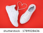 Small photo of Pair of white shoes and shoelaces in shape of heart on red background